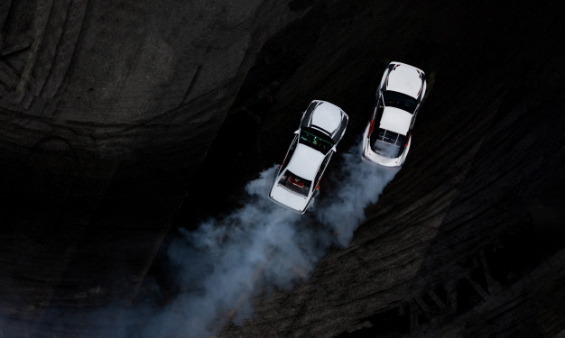 aerial-top-view-two-cars-drifting-battle-asphalt-race-track-with-lots-smoke_35024-664